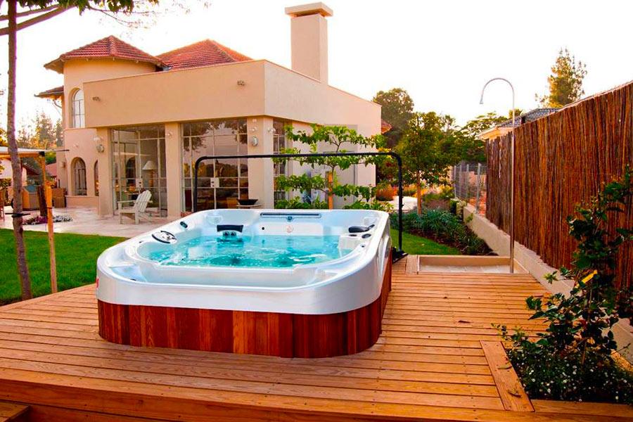 Spa à debordement installé sur une terrasse en bois dans un jardin / Coast Spa